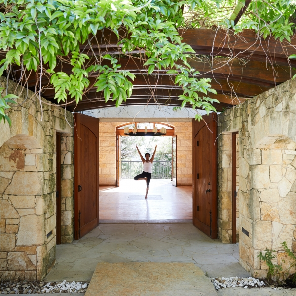 Woman makes yoga pose at the end of hallway at Miraval.