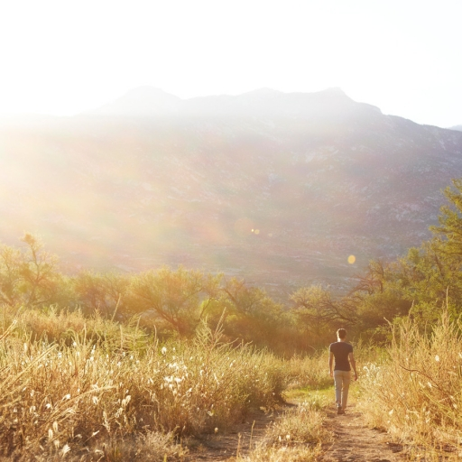 Man hikes along outdoors trail during sunset at Miraval.