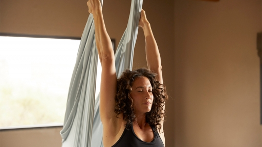 Woman performs aerial yoga stretch at Miraval.