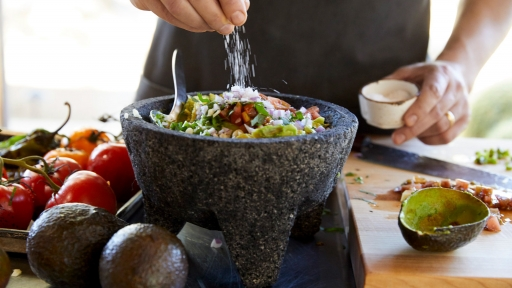 Man adds salt to avocado-centered dish at Miraval dining experience.