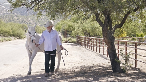 Man in cowboy hat walks white haired horse on field at Miraval.