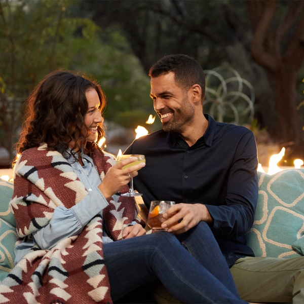 Couple enjoys drinks during sunset at outdoors firepit at Miraval.