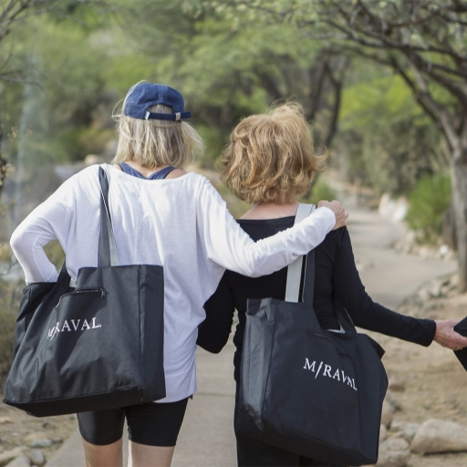 Women walk on trail with bags while talking at Miraval.