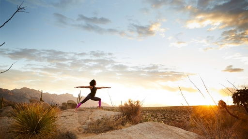 Woman experiences yoga outdoors at sundown at Miraval Arizona.