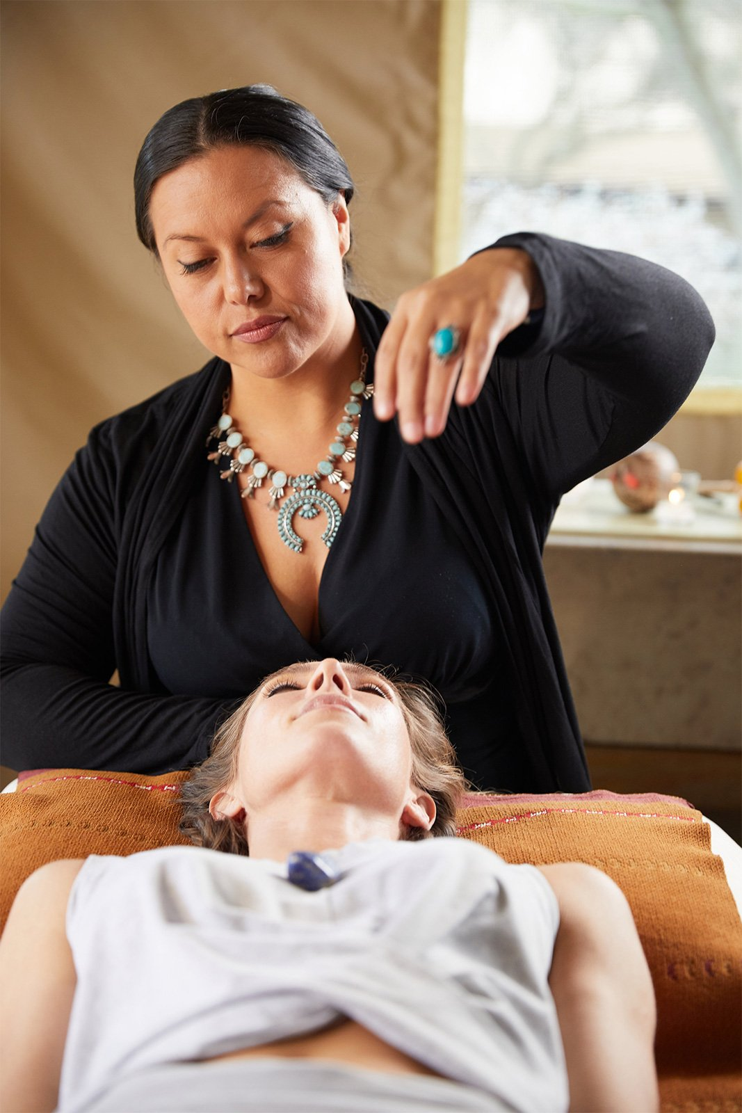 Woman holds hand over another in spa treatment at Miraval.
