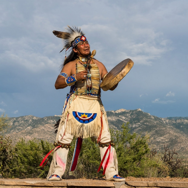 Tony Redhouse dressed up in native American outfit poses for photo at Miraval.