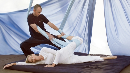 Full view of instructor helping woman during yoga stretch at Miraval.