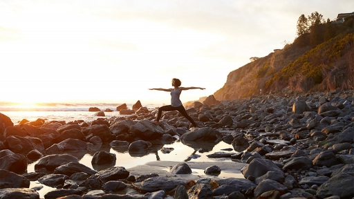 Woman experiences outdoor yoga on rocks by the ocean at Miraval.