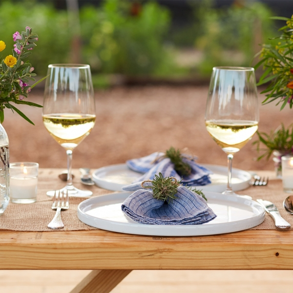 Table for two set up outdoors with wine and flowers at Miraval.
