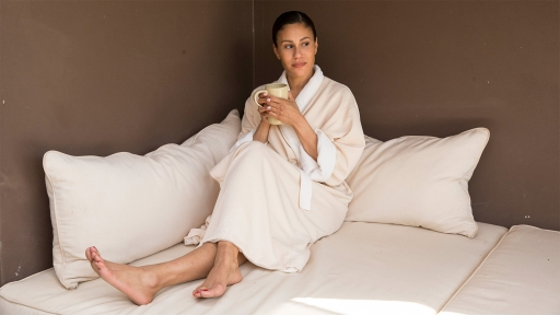 Woman enjoys cup of tea on bed while wearing comfortable robe at Miraval.