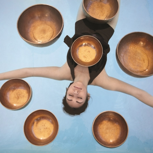 Woman floats in pool with several copper bowls floating around her at Miraval.